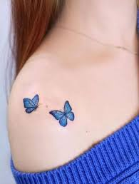 Blue Color Flying Butterfly Tattoo On Shoulder